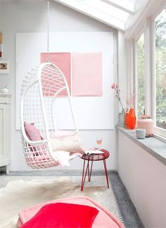 Suspended swing chair with pink accents.