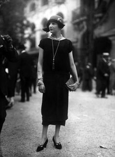 A black dress tapering in slightly at the hem, including a front panel decorated with tiny pleats. Designed by Jenny. Seeberger Freres on Getty Images