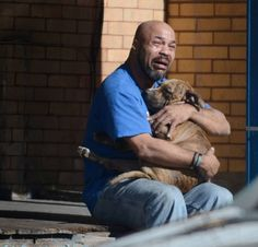 The news story behind heart wrenching photo of man holding late dog after fire