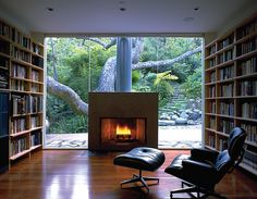 A glass wall separates two walls of books; fireplace for warmth & an Eames lounger for reading.