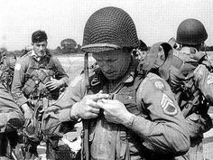 A sergeant from the 82nd Airborne Division is checking his parachute harness before getting on the planes along with others the for jump.