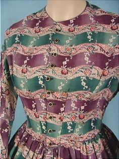 "c. 1850 cotton print gown. Neck, armscye, waist, top of sleeve flounce piped, front button closure, buttons edged with gold, bodice boned in front, lined in dark tan cotton, sleeve flounces lined with dark green cotton, cartridge pleated, one hidden side pocket in skirt, skirt unlined except for wide band of brown & white calico. Bust: 34"", Waist: 26"", length of skirt: 45""; width at hem: 104""."