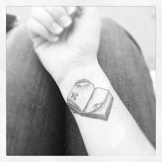 Attractive and tasteful tattoo on wrist of an old book with a FRIENDSHIP SYMBOL printed on the lower corner of the page.