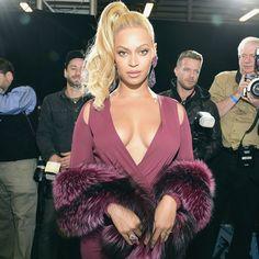 Beyoncé com vestido vinho e gola de pele.