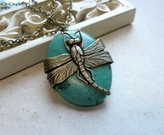 Here is a fabulous dragonfly necklace, which is comprised of one large, beautiful blue green turquoise stone, wrapped with a detailed brass