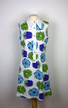 This is a eye-catching 1960s mod scooter dress. It is white with a bold purple, blue and green floral pattern. The dress features a large collar no label