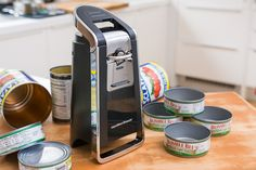 The hamilton beach smooth touch can opener sitting on a wooden kitchen table with some open cans.