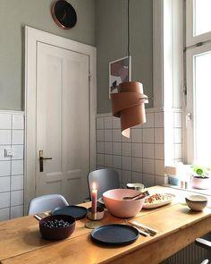 Gedeckter Esstisch in der Küche - geschwungene Lampe aus Leder/weiße Fliesen/graue Stühle
