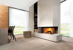 This is a #Brunner two sided fireplace in a livingroom with a plateau from stone. #fireplace #stone #design #white