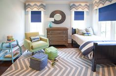 Gorgeous boy's bedroom with light blue walls and ceiling over hardwood floors layered with a white and gray chevron rug.
