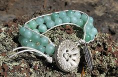 Gorgeous teal stone beads paired with an elegant antique button from Taylor's Button Shop in London, England make this bracelet a charmer and its silver feather charm ensures just that!