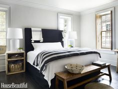 The petite scale of the Colonial-era master bedroom required Weeks to abandon symmetry and overlap one of the windows with the king-size bed. The upholstered headboard is by Restoration Hardware, and the lamps are from Ralph Lauren Home.