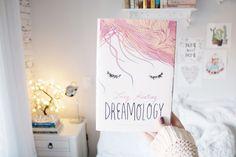 Foto de Melina Souza do livro Dreamology (young adult - jovem adulto) em um quarto clean e com detalhes fofos.