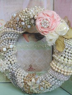 Beautiful 10 styrofoam wreath base covered in a wide rich green satin ribbon.Using strings of pearls and rhinestone and vintage jewelry, they are all entwined completely around the wreath. The wreath is accented with a beautiful spray of pink and cream satin and silk flowers with a