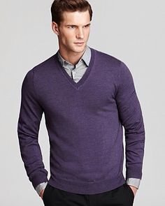 V neck purple sweater, grey shirt and black pants. No tie.