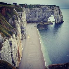 Cliffs of Etretat in Normandy, France. The white cliffs and three natural rock arches of Etretat are some of the best-known sights in Upper Normandy in France and a popular day-trip destination. Etretat is famous for its three natural arches and white chalk cliffs that tower high over the Atlantic Ocean.