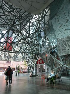 Atrium at Federation Square in Melbourne, Australia - This atrium uses steel and glass to create the look of a bird's nest. This atrium is part of Federation Square, which is an open square in the heart of Melbourne. They relate to each other because the atrium is open to the outside world and provides a covered public space.