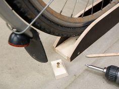 """Mit Fahrradständern ist das oft so eine Sache. Entweder die Räder stehen auf dem Boden. Das spart keinen Platz. Oder der Ständer hält die Räder senkrecht an der Wand. Das verlangt einen erheblichen Kraftaufwand, um ein Rad mal schnell einzuhängen. Unser Ständer ist ein guter Kompromiss – er verläuft nämlich schräg. Und zwar so schräg, dass die Räder nur etwa die Hälfte ihrer Länge an Raum verschwenden, sie aber immer noch bequem in die """"Fahrrinnen"""" eingeschoben werden können."""