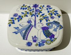 Adorable Figgjo Flint Norway Lotte Turi Lidded Square Butter or Candy Dish. Adorned with a silk-screened image of a woman lounging with a teapot and teacup, a tree and flowers in blues, green and purple.