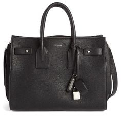 SAINT LAURENT SMALL SAC DE JOUR TOTE - BLACK  DETAILS Subtle and elegant, this beautifully structured little tote is cast in richly grained leather, with accordioned sides that provide a deceptive amount of storage space. A signature covered padlock swings from the rolled carry handles, while a foiled logo stamp adds an iconic finishing touch.