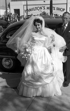 """At 18 years old, Elizabeth Taylor arrives to marry the hotel heir Conrad """"Nicky"""" Hilton at the Bel-Air Country Club. This was the first of her eight marriages, and for the occasion she wore a gown given to her by MGM Studios."""