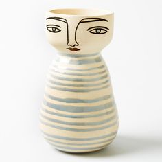 Cool and nonchalant, Greta vase has a bisque base with hand painted face detail and gloss pale blue stipe body pattern. Filled with any type of flowers or green