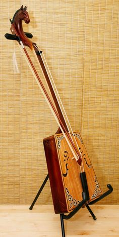 """The Morin Khuur, (aka """"Horse-head Fiddle"""") is the national instrument of Mongolia. It always has some kind of horse's head as a headstock --- https://www.pinterest.com/lardyfatboy/"""