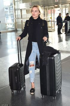Arriving in style! Margot Robbie sported a casual chic look as she jetted into JFK Airport in New York on Thursday, wearing ripped jeans, a black turtleneck and navy coat with canvas flats