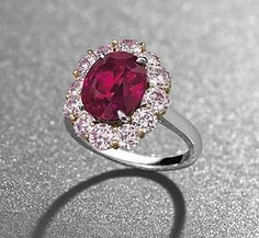 AN EXCEPTIONAL RUBY AND COLOURED DIAMOND RING. Set with an oval-shaped ruby, weighing approximately 5.09 carats, to the pink diamond surround, mounted in platinum and gold.