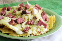 Corned Beef and Cabbage Nachos | Meat, some veggies, and a white cheese sauce makes perfect sense on top of a huge pile of tortilla chips. Corned beef has so much flavor that it can really shine through with the milder flavors of the cabbage and cheese sauce. - @stayathomechef