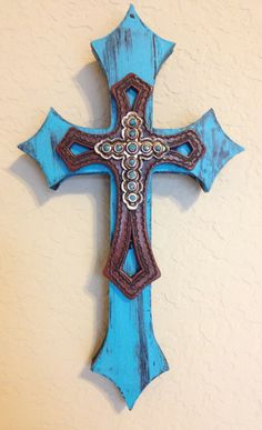 """Miniature wooden, double layer, wall cross. Painted with black and turquoise acrylic paint. The piece is topped with a faux stitched leather cross with cutouts and then a silver cross with scalloped edges and turquoise accents. Dimensions are approximately 4"""" x 7"""". Each cross is handmade with love and truly one of a kind."""