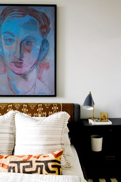 Oversized artwork above the bed with black nightstand and patterned headboard