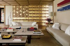 An overscale Danh Vo American flag painting and a two-part wall piece by John McCracken survey a living area's Luis Bustamante–designed cocktail tables and sofas, the latter upholstered in a Ralph Lauren Home linen. The tabletop sculpture is by Alexander Calder. - photo: Ricardo Labougle