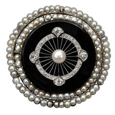 Art Deco Onyx Pearl Diamond Gold Platinum Brooch. A circular brooch in gold, onyx and pearls, with geometrical detail in platinum and diamonds and central pearl. Central pearl measures approximately 0.50 cm. c 1930s