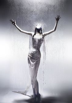 A model poses behind a sheet of glass before walking the runway at Alexander McQueen's 2004 catwalk show, Black. Made up of multiple collections, this special show was staged by American Express, a longtime supporter of McQueen. This iconic look comes from The Golden Shower Spring/Summer 1998. This image was photographed backstage by Nick Knight and is part of the ongoing Unseen McQueen series, launched alongside Savage Beauty, which is currently showing at the V&A Museum in London.