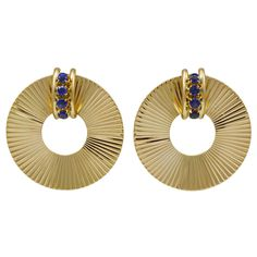 """Tiffany & Co. Retro Sapphire Gold Earrings. Large Retro clip earrings made and signed by Tiffany & Co. Set in 14K yellow gold with a row of faceted bright sapphires. Very crisp and chic. A very good size, 1 1/4"""" diameter. Wearable, a signature earring."""
