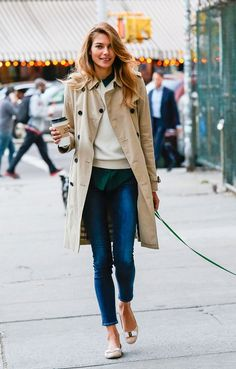 Cropped jeans with a collared shirt layered under a sweater and a trench coat with neutral ballet flats