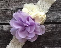 """Headband with three beautiful flowers and boa feathers on ivory elastic lace. All my headbands are felt backed for comfort. All my headbands are made to order and can be customized with different colors to fit your needs. Size recommendations: Newborn: 13 0-3 Months: 14 3-6 Months 15 6 Months-3 Years: 16 4 Years- Teens: 17 If no size is selected size 15"""" will be sent.  Please Be Aware: Some of my products may contain small parts which can pose a choking hazard. Do not leave small children…"""