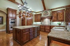 Open kitchen in shades or brown // Two islands, two sinks, light granite, vaulted and beamed ceiling, custom cabinetry