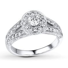 A halo of diamonds encircles the round diamond center of this spectacular engagement ring for her. Additional round diamonds sparkle along the band. Milgrain detailing completes the look. The ring, styled in 14K white gold, has a total diamond weight of 1 carat. Diamond Total Carat Weight may range from .95 - 1.11 carats.