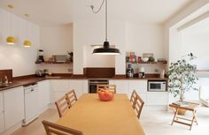 Warm minimalist kitchen with white handle-less doors and worktop made from…