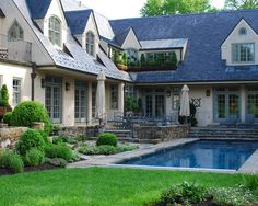 L shape with multiple blue/grey trimmed french doors to view and access pool from many rooms simple,elegant landscape