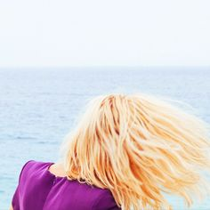 Blonde hair toss against blue ocean and purple dress // Instagram by @Jimmy_Marble