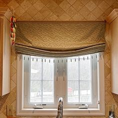 Kitchen Curtains- Soft Roman Shade - The soft roman shade adds a touch of elegance to the tiled walls and wood cabinets of the kitchen. It is mounted on board. The tassels and the rope on the top add finishing touches as they coordinate perfectly with the fabric.