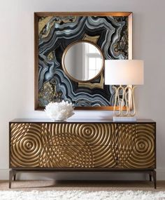 The rustic gold fronts on the Ripples cabinet resemble circles of movement on water. Designed by Mark McDowell for John-Richard, this beautiful furniture piece is enhanced by a dramatic meld of texture and pattern. Also, nature inspired, the Selenite Spar Stone bowl and the reverse hand-painted Agate mirror bring unique elements to any interior. #cabinet #interiordesign #gold #luxury #furniture #glamorous #ripples #marble #mirror #lamp