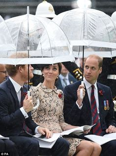 Kate sheltered from the rain under her husband's umbrella
