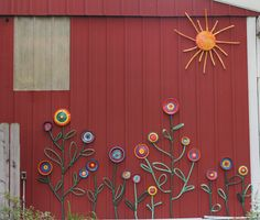 Flower garden on the side of our barn.  Painted pot lids, pan lids & cake pans for the flowers. Painted a small garbage can lid for the sun. Used old hose as is for stems and leaves. Painted old hose for rays of the sun.