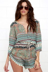 Your wandering spirit just might gravitate toward the Mila Gypsy Playsuit Turquoise Print Romper! Silky woven rayon is adorned in a turquoise, orange, red, green and ivory print over a relaxed bodice (with partial button placket) and half sleeves. Drawstring waist cinches above shorts with adjustable button-tab sides.