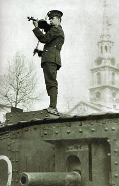 Soldier playing the violin on a tank during WWI.