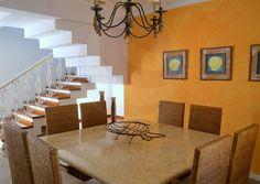 No caminho para a escada que conduz ao pavimento superior, a sala de jantar conta com mesa com tampo de mármore e acomoda até 8 pessoas nas cadeiras revestidas com fibra treliçada. — em Edmundo Imóveis.